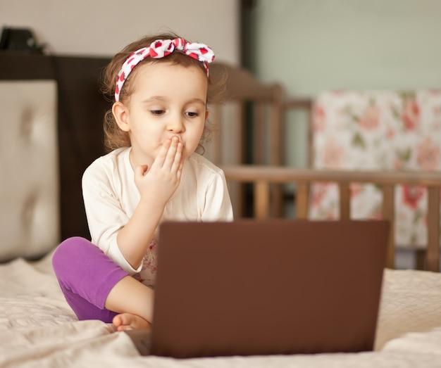 Piccola ragazza sveglia che si siede sul letto e che per mezzo di un taccuino del computer portatile della compressa digitale. chiamate online amici o genitori.
