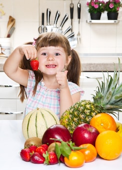 Piccola ragazza sveglia che tiene e che mangia una fragola nella cucina