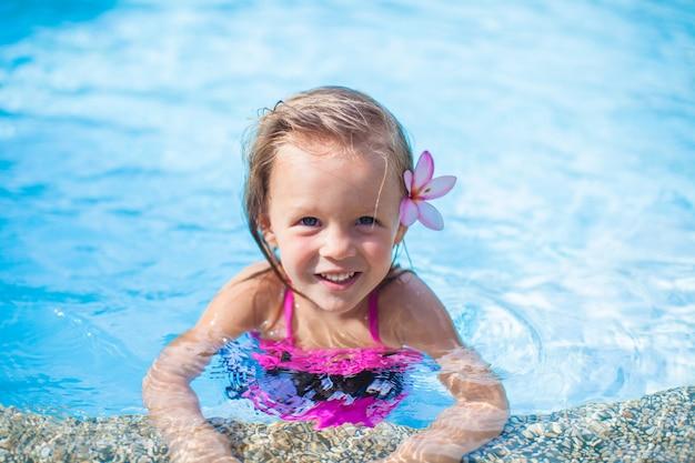 Piccola ragazza sveglia con il fiore dietro il suo orecchio nella piscina