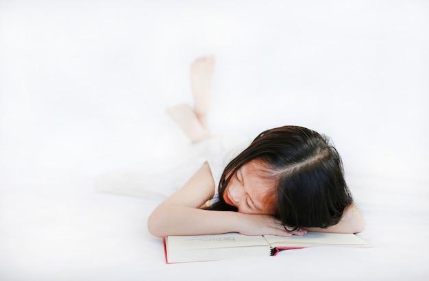 Piccola ragazza sveglia del bambino asiatico che si trova sul libro di hardcover sul letto sopra fondo bianco.