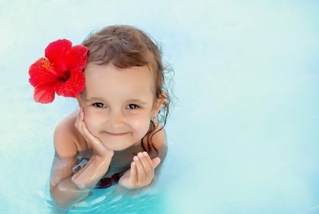 Piccola ragazza sveglia del bambino con il fiore rosso dietro il suo orecchio che si siede in un'acqua blu