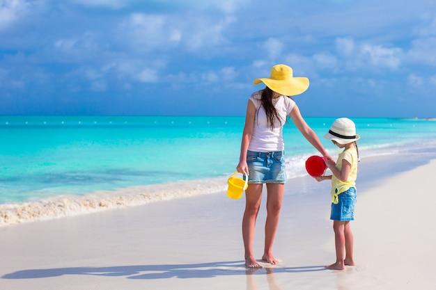 Piccola ragazza sveglia e giovane madre che giocano alla spiaggia tropicale