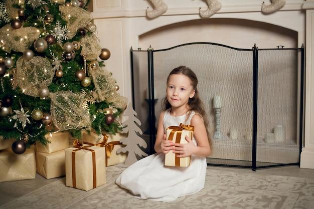 Piccola ragazza sveglia in vestito che si siede vicino all'albero di natale e che tiene i regali.