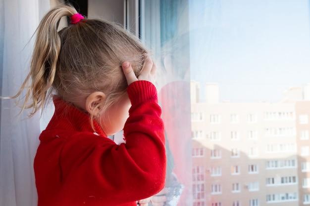 Piccola ragazza triste che guarda fuori dalla finestra. rimani a casa in quarantena. concetto di isolamento. epidemia di virus, crisi medica sanitaria