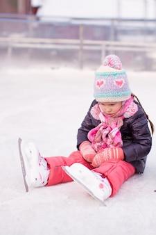 Piccola ragazza triste che si siede su una pista di pattinaggio dopo la caduta