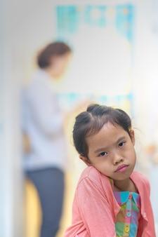 Piccola ragazza triste o arrabbiata del fronte sulla mamma occupata in smart phone