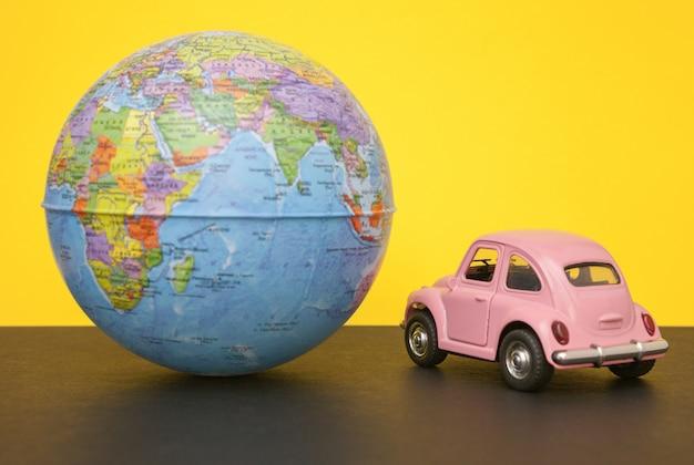 Piccola retro automobile rosa con la sfera del globo del mondo.