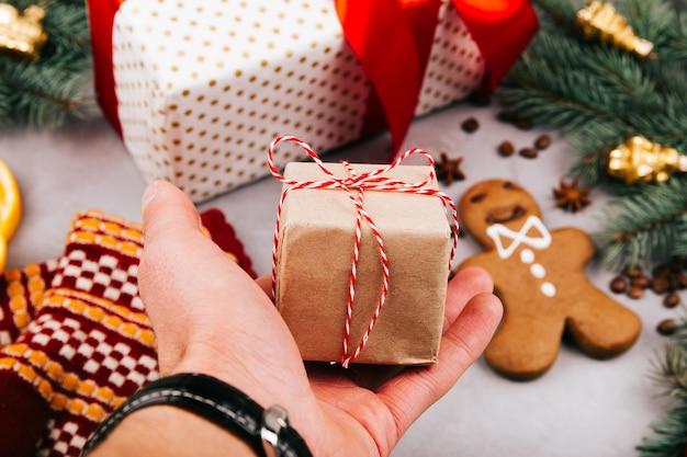 Piccola scatola regalo di natale in mano dell'uomo