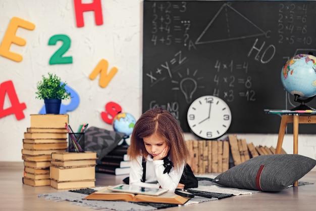 Piccola scolara astuta con la compressa digitale in un'aula.