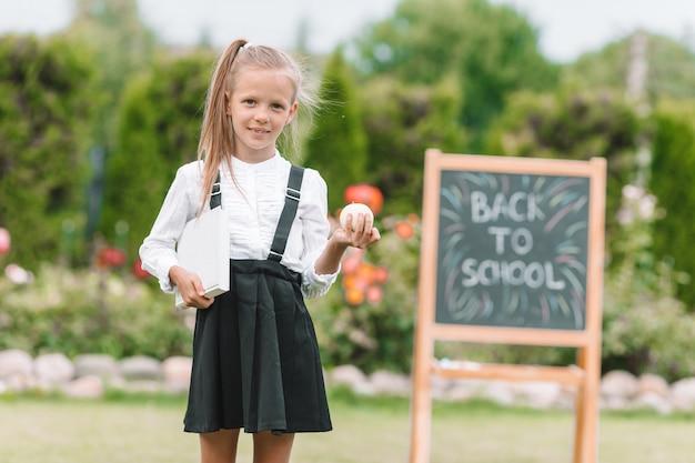 Piccola scolara felice con una lavagna all'aperto