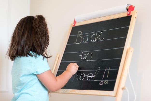 Piccola scolara sveglia che scrive in lavagna con testo di nuovo a scuola.