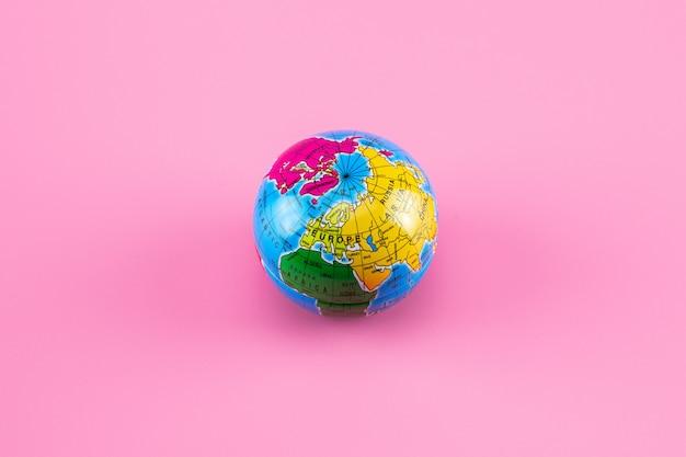 Piccola sfera del globo del mondo sul rosa.