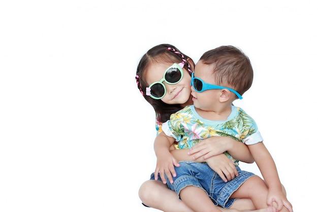 Piccola sorella asiatica del ritratto che abbraccia fratello piccolo che porta un vestito e gli occhiali da sole da estate dei fiori isolati. estate e concetto di moda.