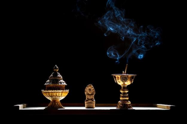 Piccola statua di buddha con porta incenso con cono in fiamme.