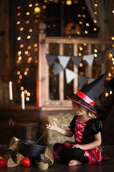 Piccola strega in costume e cappelli evocano pentola, infanzia halloween,