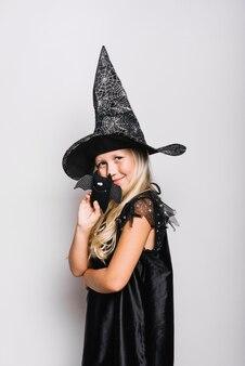 Piccola strega in posa con pipistrello giocattolo