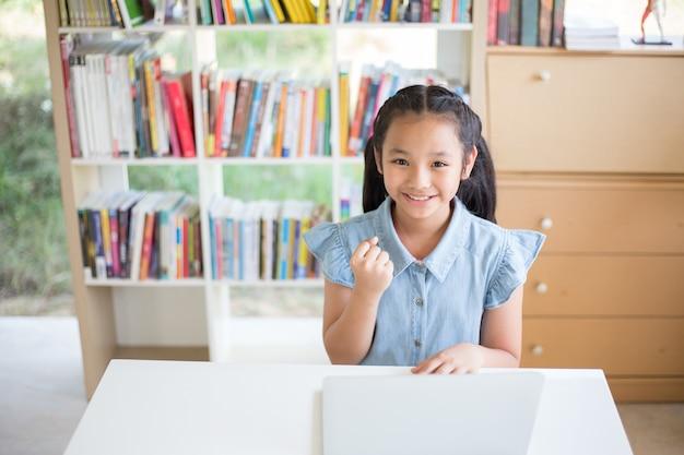 Piccola studentessa con computer portatile alla scrivania in libreria e fighto recitazione