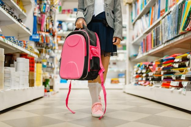 Piccola studentessa con lo zaino in mano allo scaffale in cartoleria. bambino femminile acquisto di forniture per ufficio in negozio, scolaro in supermercato