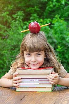 Piccola studentessa con una mela rossa. messa a fuoco selettiva natura.