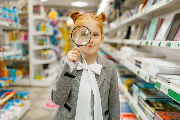 Piccola studentessa scegliendo lente d'ingrandimento, shopping in cartoleria. bambino femminile acquisto di forniture per ufficio in negozio, scolaro in supermercato