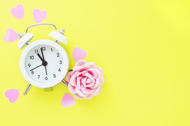Piccola sveglia bianca, cuori rosa e carta rosa rosa su uno sfondo giallo brillante. spazio per il testo.