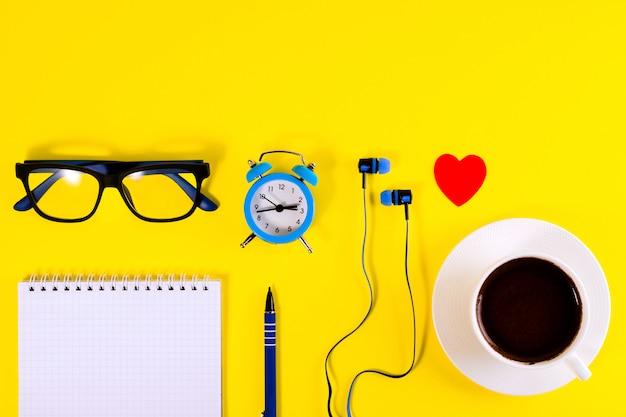 Piccola sveglia blu, cuore rosso, auricolari, occhiali e taccuino, penna, su sfondo giallo.