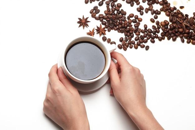 Piccola tazza del chicco di caffè in pieno del chicco di caffè isolata su bianco