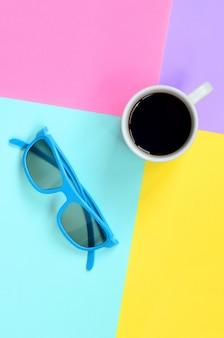 Piccola tazza di caffè bianco e occhiali da sole blu