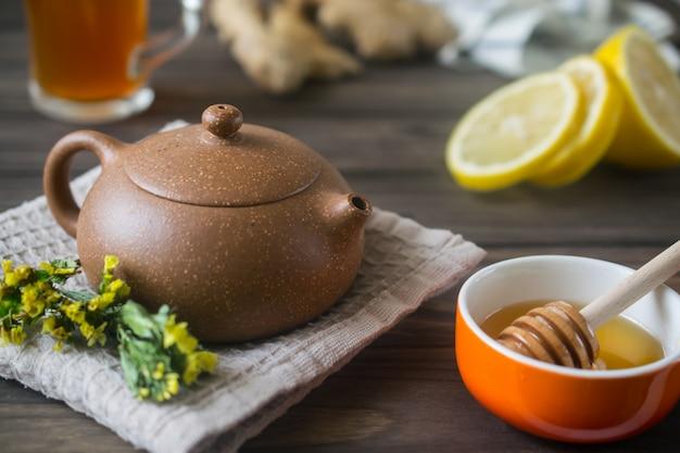 Piccola teiera in ceramica con tisana sul tavolo di legno con limone e miele
