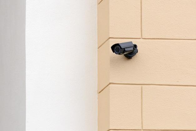 Piccola telecamera di sorveglianza di sicurezza nera sulla facciata dell'edificio
