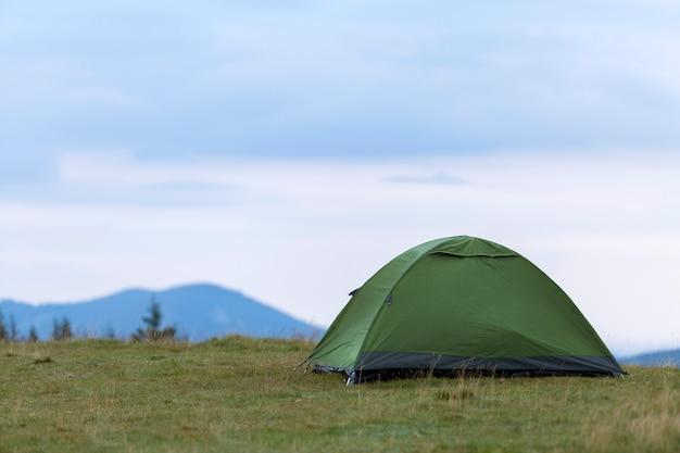 Piccola tenda turistica sulla collina erbosa della montagna.