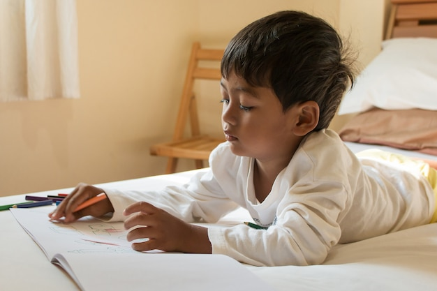 Piccola vernice asiatica del ragazzo sul libro bianco nella stanza