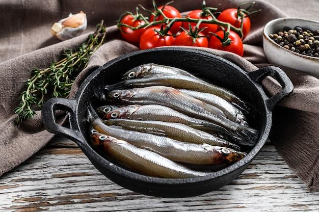 Piccole acciughe di pesce crudo con pepe e timo in padella