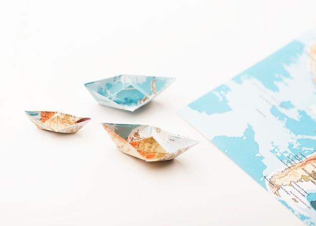 Piccole barche di mappa del mondo di carta ad alto angolo