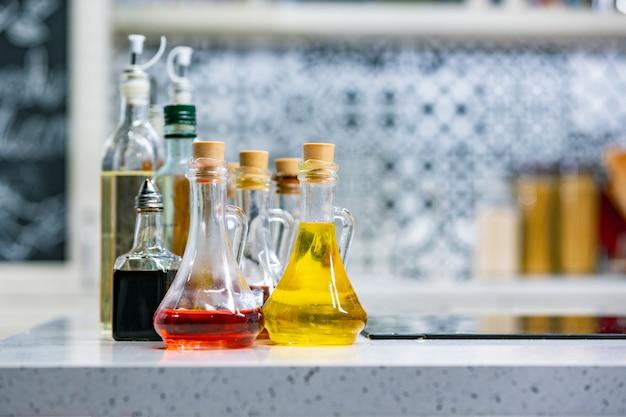 Piccole bottiglie di olio d'oliva aromatizzato e aceto balsamico in cucina copia spazio.