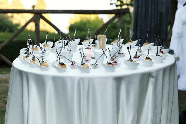 Piccole ciotole con spuntini serviti sul tavolo bianco all'esterno
