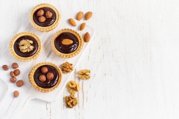 Piccole crostate al cioccolato ricco di noci su uno sfondo bianco