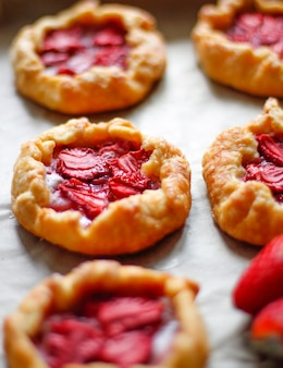 Piccole crostate rustiche della torta di galette della fragola con zucchero a velo sulla teglia