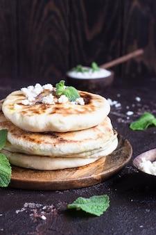 Piccole focacce di cipolla, menta e formaggio servite su un piatto di legno. gozleme.