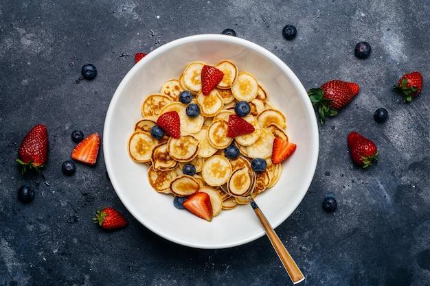 Piccole frittelle per colazione. frittelle con fragole e mirtilli cotti al mattino per la colazione nella cucina di casa.