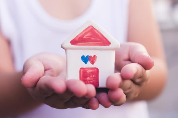 Piccole mani del bambino che tengono casa
