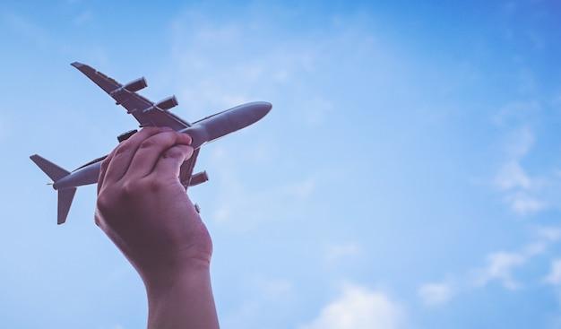 Piccole mani del bambino che tiene aeroplano
