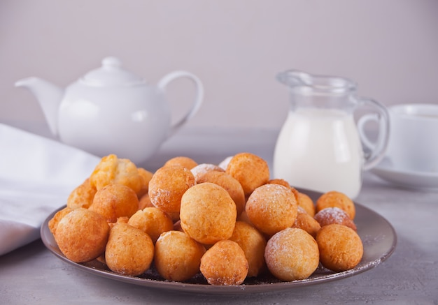 Piccole palline di ciambelle di ricotta fatti in casa appena sfornati in un piatto su uno sfondo grigio.