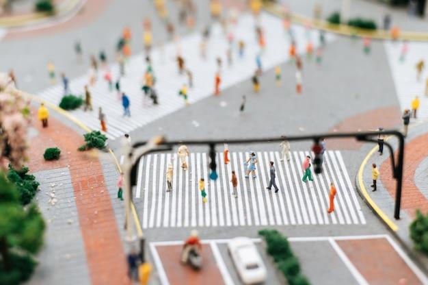 Piccole persone o persone si intrecciano camminando su molte strade.