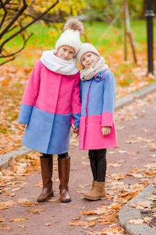 Piccole ragazze adorabili all'aperto al giorno soleggiato soleggiato di autunno