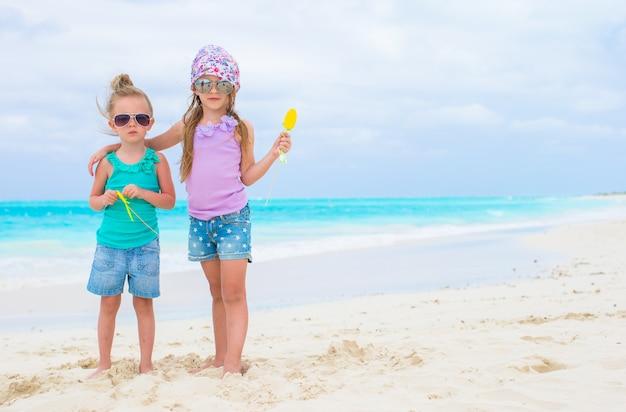 Piccole ragazze adorabili durante la vacanza tropicale della spiaggia