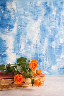 Piccole rose e vecchio libro su sfondo blu