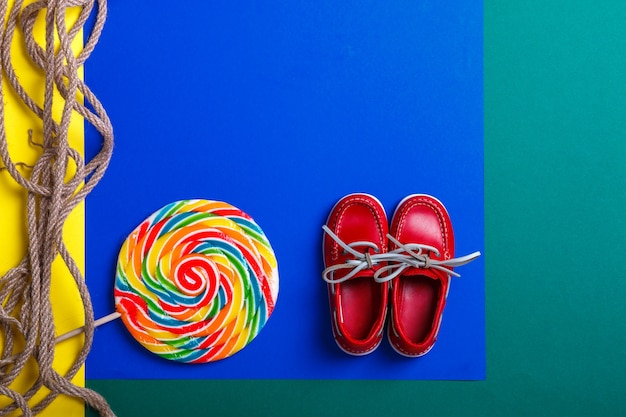 Piccole scarpe rosse da barca vicino alla grande lecca-lecca multicolore e corda