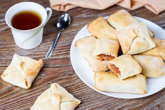 Piccole torte di mele o grappoli di mela con cannella su un piatto bianco con una tazza di tè e mele mature in background