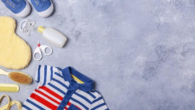 Piccoli accessori del neonato o del bambino su fondo grigio